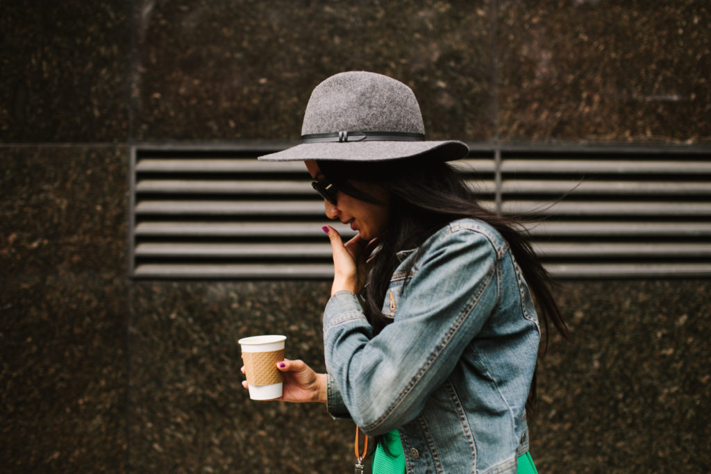 Young Woman Wearing A Hat And Sunglasses, Holding A Cup Of Coffee And Walking.