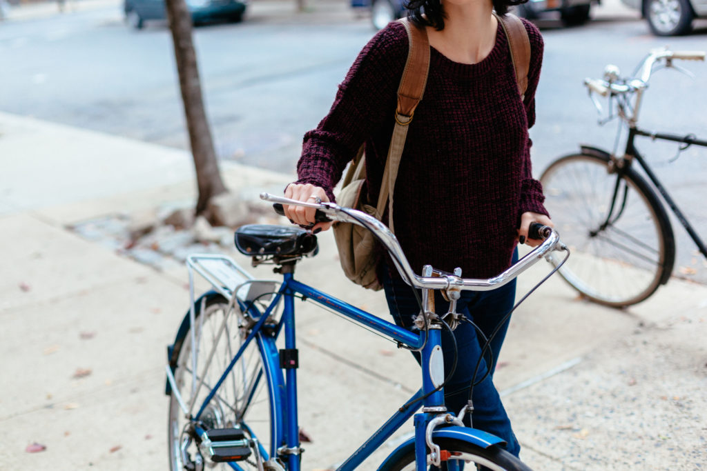 Woman walking on the sidewalk holding a bicycle