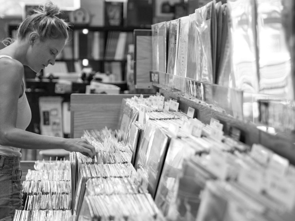 young woman thumbing through vinyl records at a record shop