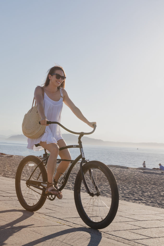 Marsis Seattle young lady on a cruiser bike riding by a beach
